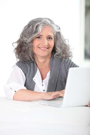 Mujer que usa su computadora port�til Foto de archivo - 14003591