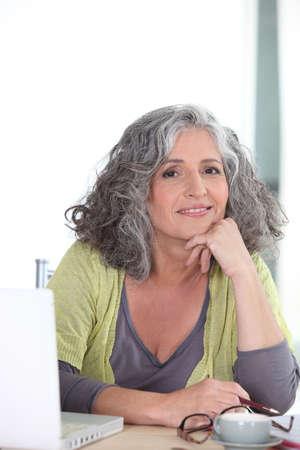 vejez feliz: Anciana en frente de su computadora portátil Foto de archivo