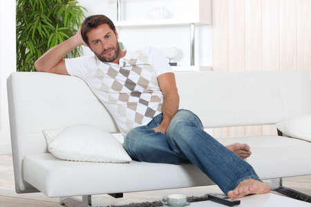 barefoot man: A man resting on his sofa. Stock Photo
