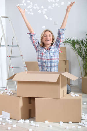 gleeful: Woman joyously unpacking boxes Stock Photo
