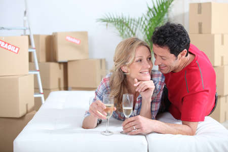 removals: Couple lying on bed celebrating moving into new home