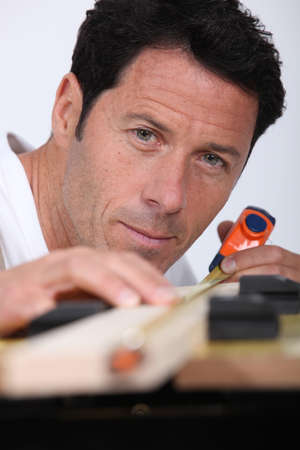 Closeup of a man measuring a piece of wood with a tape measure photo
