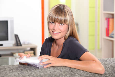 Young woman with a blunt fringe choosing a CD photo