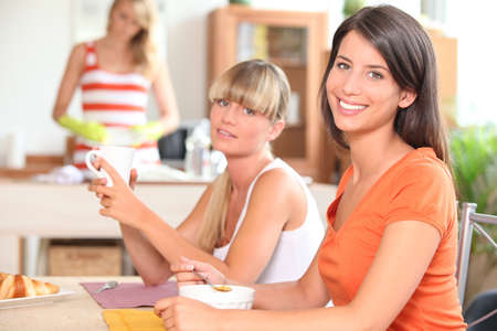 Three young women having breakfast at home Stock Photo - 13959694