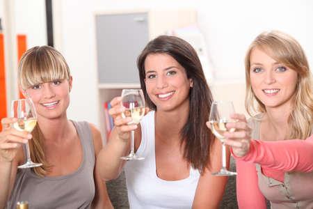 bebiendo vino: Tres mujeres brindando con una copa de vino