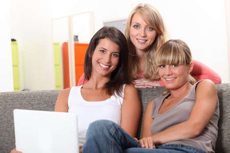 clique: Three girls relaxing at home in front of laptop computer