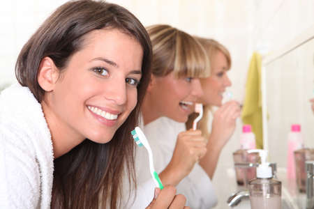 getting ready: Three young women brushing their teeth Stock Photo