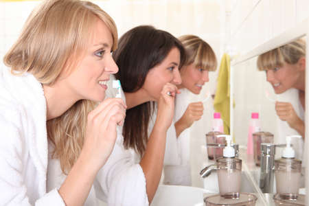 Three women brushing their teeth photo