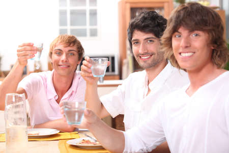 Three young men eating a meal together and drinking water photo