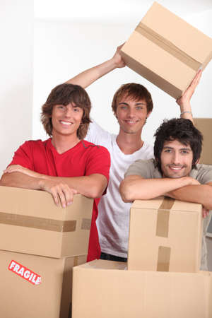 three young people in a room full of cardboard boxes photo