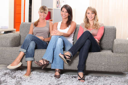 Young women sitting on a sofa photo