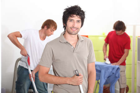 Three male housemates cleaning photo