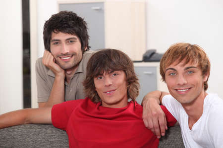 chilling out: Three male students gathered on the sofa Stock Photo