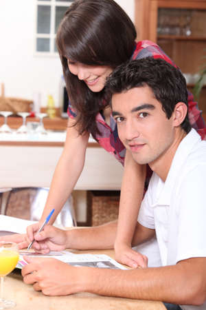 annotations: Couple writing on the kitchen table Stock Photo