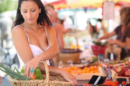 sexy brunette buying vegetables at open air market photo