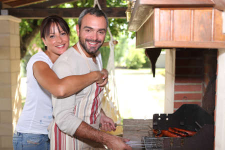 Smiling couple preparing barbecue photo