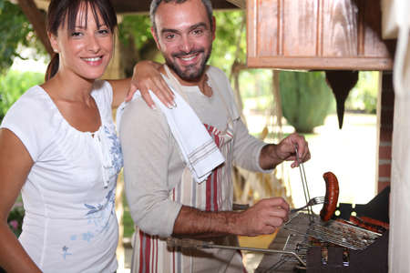 Couple cooking sausages on the barbecue photo