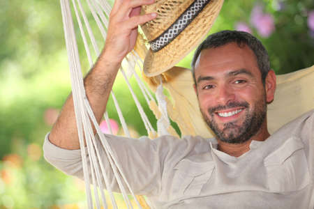 greets: Man with hat on hammock