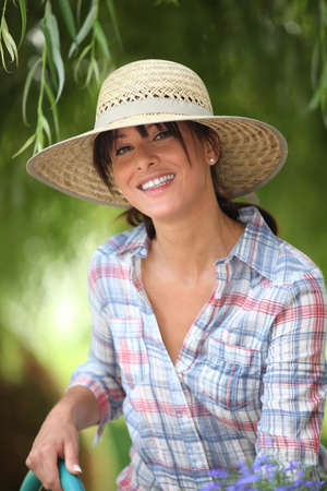 young woman with a straw hat is watering in her kitchen garden photo