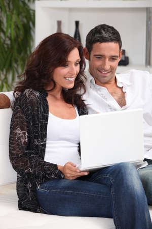 couple with laptop in lounge photo