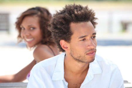 Woman looking at her pensive boyfriend photo