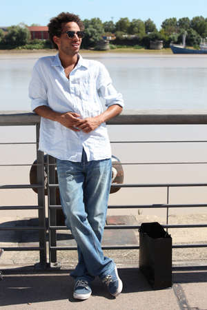 laid back: Man strolling along the waterfront on a summers day Stock Photo