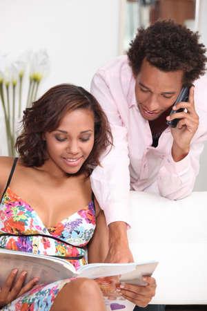 llamando: una mujer joven y metis su novio viendo un folleto y llamar a alguien