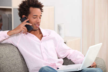young man sitting on sofa with laptop making a call photo