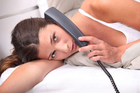 Woman talking on the phone in bed photo