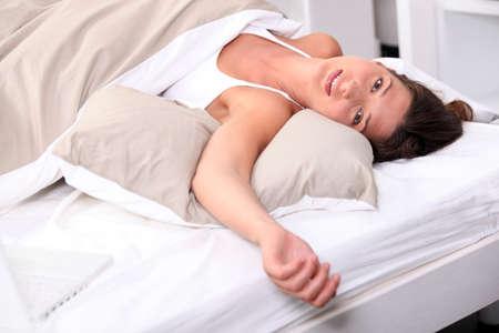 lying down: Woman sprawled in bed