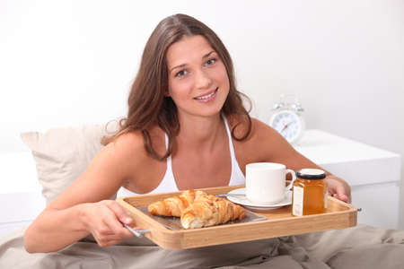 Woman having breakfast in bed photo