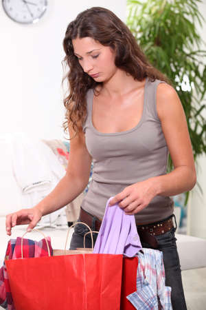 Woman searching through shopping bags photo