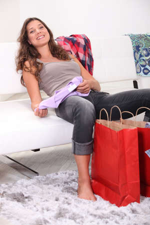 Exhausted brunette sat on couch with her purchases photo