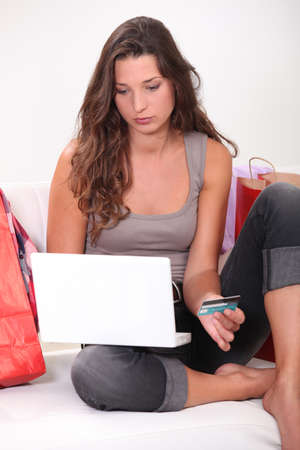 Brunette sat at home shopping on-line photo