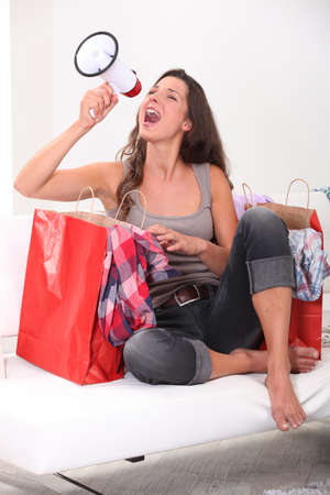 Studio shot of a woman with shopping bags and a loudspeaker photo