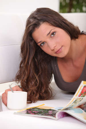 Woman reading a book while drinking a cup of tea photo