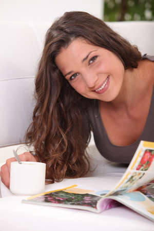 Woman laying on sofa with cup of coffee and magazine photo