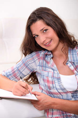 Teenager writing in notebook Stock Photo - 14026977