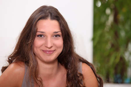smirk: Brunette relaxing at home Stock Photo