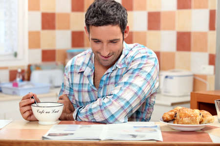 Smiling man having continental breakfast in his kitchen with a newspaper photo