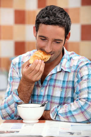 Smiling man eating croissant for breakfast with a magazine photo