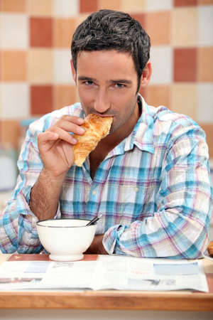 Handsome man eating a croissant photo