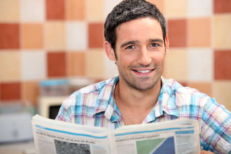 adult magazines: Man reading a newspaper in the kitchen