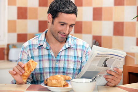 Man reading the newspaper while having breakfast photo
