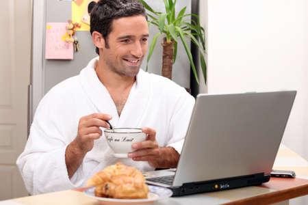 levantandose: El desayuno de los hombres con el ordenador Foto de archivo