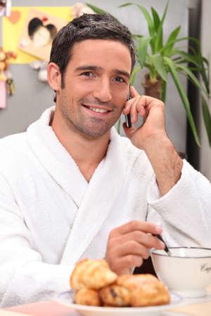 bath gown: Man sat at home having breakfast