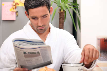 leisurely: Man having a leisurely breakfast while reading the paper