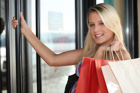 Blond woman opening shop door Stock Photo - 13957965