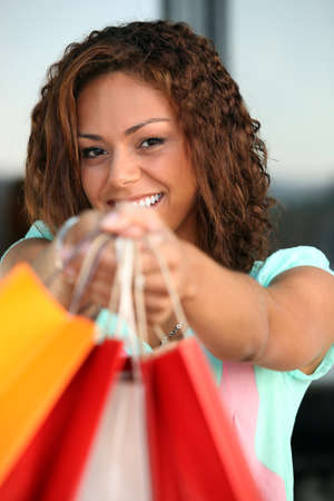 Young woman with a pile of shopping bags photo