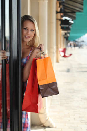 out door: blonde woman entering in a store Stock Photo